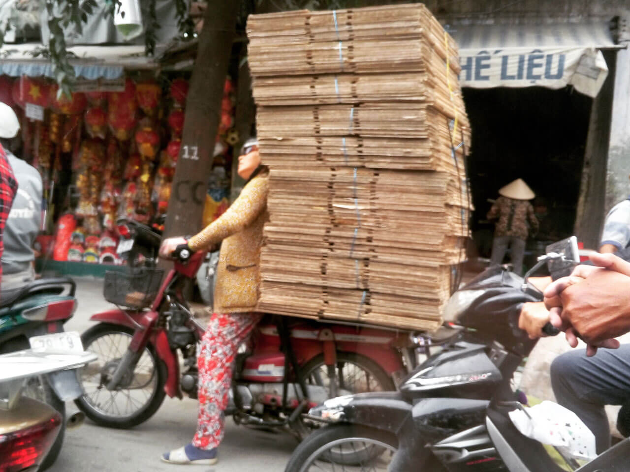 Vietnamese woman on a bike with a bundle of boxes behind her back